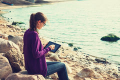Girl using digital tablet at sea Stock Image