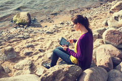 Girl using digital tablet at sea Stock Photo