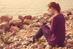 Girl using digital tablet at sea Royalty Free Stock Photo