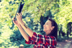 Girl using digital tablet taking picture of herself. Technology internet modern lifestyle concept. Girl using digital tablet taking picture of herself. Selfie Stock Image