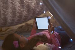 Girl using digital tablet under blanket in bedroom. At home Stock Image