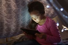 Girl using digital tablet under blanket in bedroom. At home Stock Images