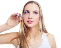 Girl using an eyelash curler Stock Photography