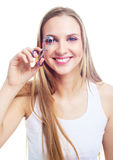 Girl using an eyelash curler Royalty Free Stock Image