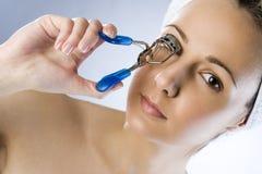 Girl using eyelash curler and makes eyelashes wider. Girl using eyelash curler and makes her eyelashes wider royalty free stock image
