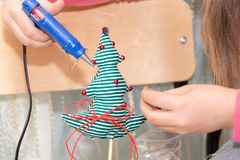 Girl using glue to decorate Christmas tree. Handmade present stock photo