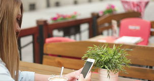 Girl using her mobile phone in cafe. Portrait of beautiful girl using her mobile phone in cafe stock video footage