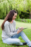 Girl using her tablet pc while sitting in a park Stock Photos