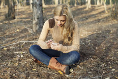 Girl using internet wireless on smartphone in natu Royalty Free Stock Photo