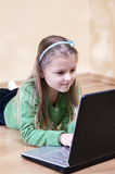 Girl using laptop. Portrait of cute blond haired girl lying on floor using laptop computer Stock Images