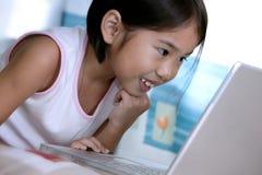 Girl using laptop. Kid using laptop to communicate Royalty Free Stock Photos