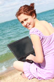 Girl using a laptop. On the tropical beach Royalty Free Stock Photography