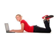 Girl using laptop. Girl lying on floor using laptop royalty free stock image