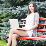 Girl using a laptop on a bench Stock Images