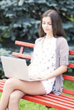 Girl using a laptop on a bench Stock Image