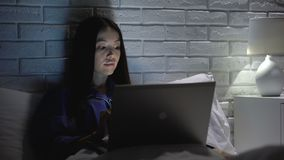 Girl using laptop and cellphone to synchronize account data, online applications. Stock footage stock footage
