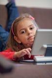 Girl using a laptop for children. Little girl with laptop for children lying on a sofa Stock Image
