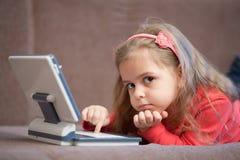 Girl using a laptop for children. Little girl with laptop for children lying on sofa Royalty Free Stock Photos