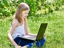 Girl using laptop on grass. Outdoor Stock Photo