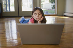 Girl Using Laptop On Hardwood Floor Royalty Free Stock Images