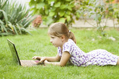 Girl using laptop in the meadow. Little girl using laptop in the garden Royalty Free Stock Image
