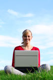 Girl using laptop outdoors. Young woman working on laptop outdoors Stock Photo