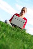 Girl using laptop outdoors. Young woman working on laptop outdoors Royalty Free Stock Photo