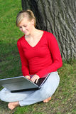 Girl using laptop outdoors. Young woman working on laptop outdoors Stock Image