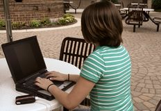 Girl using laptop outside. Girl using laptop in courtyard of school while listening to music Royalty Free Stock Image