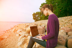 Girl using laptop at sea Stock Image