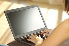 Girl using laptop and showing a blank monitor. Sitting on a couch in the living room at home with a warm light in the background Stock Image