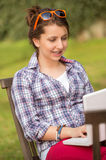 Girl using laptop sitting bench at park Stock Image