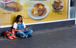 Girl using a laptop sitting on the street. Auckland, New Zealand - February 17, 2017: Young girl using a laptop, sitting on the street at a Mac Donald store Stock Image