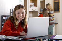 Girl using laptop to do homework Royalty Free Stock Image