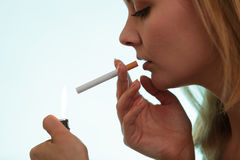 Girl using lighter to light cigarette. Royalty Free Stock Photos