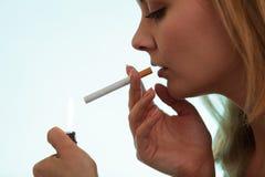 Girl using lighter to light cigarette. Royalty Free Stock Photos