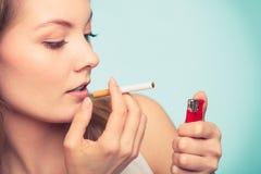 Girl using lighter to light cigarette. Stock Photos