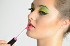 Girl using lip gloss Stock Photo