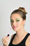 Girl using lip gloss Royalty Free Stock Photos