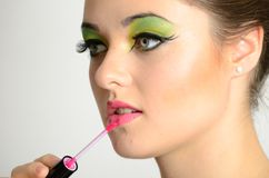 Girl using lip gloss Royalty Free Stock Image