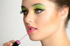 Girl using lip gloss Royalty Free Stock Image