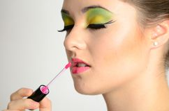 Girl using lip gloss Stock Images
