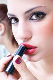 Girl using lipstic Stock Images