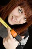 Girl using measuring tape. Beautiful redhead girl using measuring tape in workshop and pointing at 25cm Studio shot Stock Image