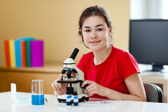 Girl using microscope Stock Photo