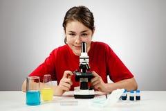 Girl using microscope Stock Photo