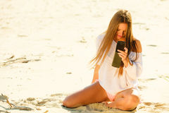 Girl using mobile phone on beach Royalty Free Stock Photography