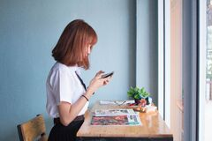 Girl using mobile phone at home Royalty Free Stock Image