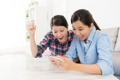 Girl using mobile smartphone playing game. Beautiful girl using mobile smartphone playing online 3D video game and sister celebrating winning showing gesture stock photography