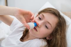 Girl Using Nasal Spray Royalty Free Stock Photography